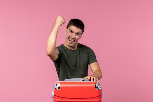 Vista frontale giovane maschio che si prepara per le vacanze e si sente felice su una scrivania rosa