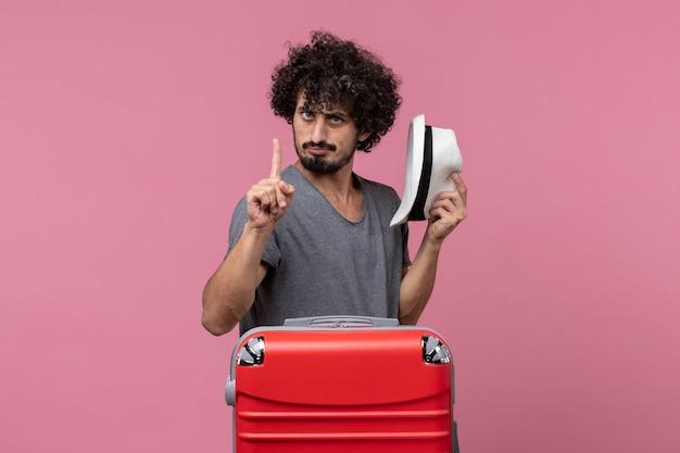 Vista frontale giovane maschio che si prepara per la vacanza tenendo il cappello sullo spazio rosa pink