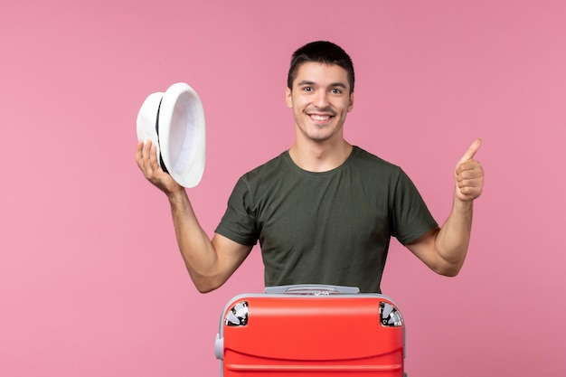 Front view young male preparing for vacation holding hat smiling on pink space
