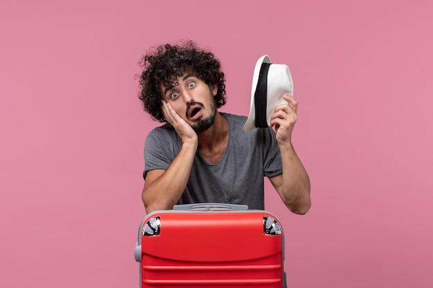 Giovane maschio di vista frontale che si prepara per le vacanze sulla scrivania rosa pink