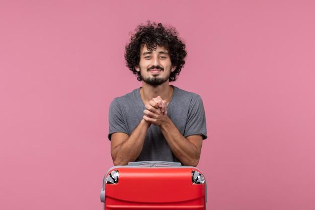 Giovane maschio di vista frontale che si prepara per la vacanza che sorride sullo spazio rosa