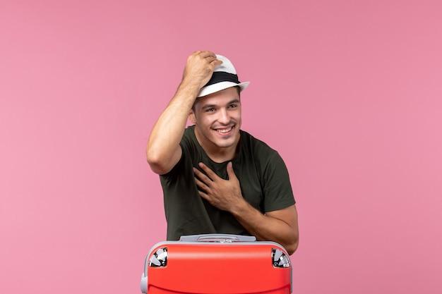 Vista frontale giovane maschio che si prepara per le vacanze indossando cappello su spazio rosa