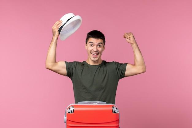 Giovane maschio di vista frontale che prepara per la vacanza con la grande borsa sullo spazio rosa pink