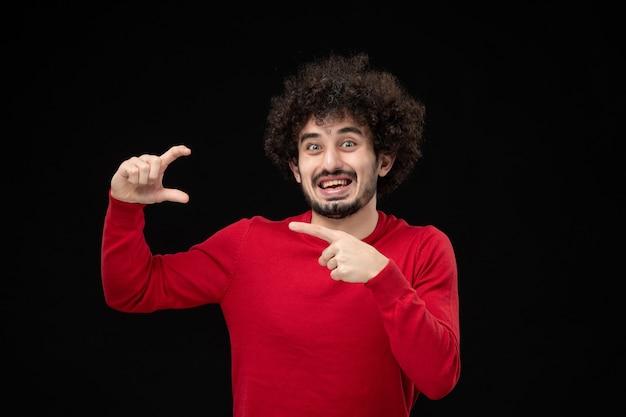 Vista frontale del giovane maschio in camicia rossa sul muro nero