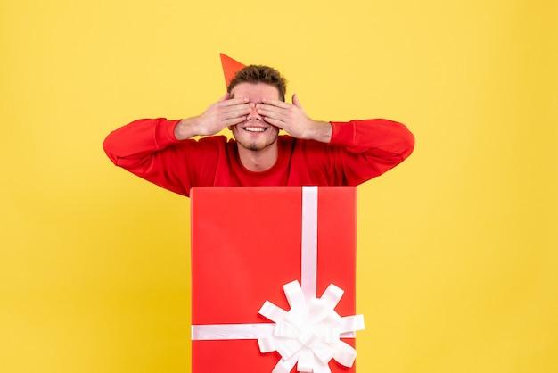 Giovane maschio di vista frontale in camicia rossa all'interno della scatola attuale