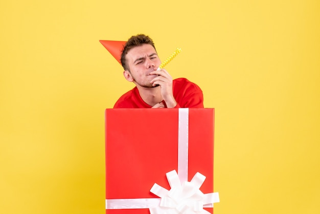Front view young male in red shirt sitting inside present box