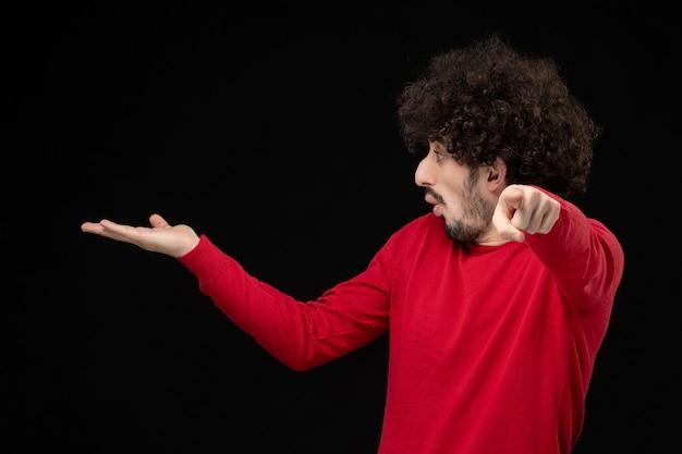 Vista frontale del giovane maschio in maglione rosso sul muro nero