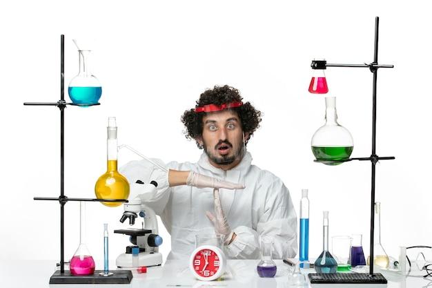 特別なスーツを着て、白い壁に保護ヘルメットをかぶった正面図若い男性科学者