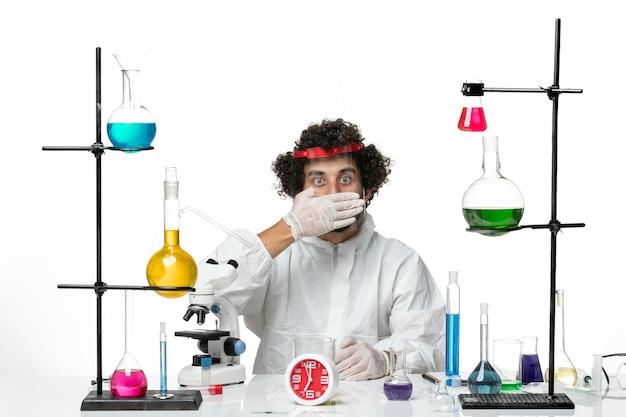 특수 양복과 흰 벽에 보호용 헬멧을 착용하는 전면보기 젊은 남성 과학자
