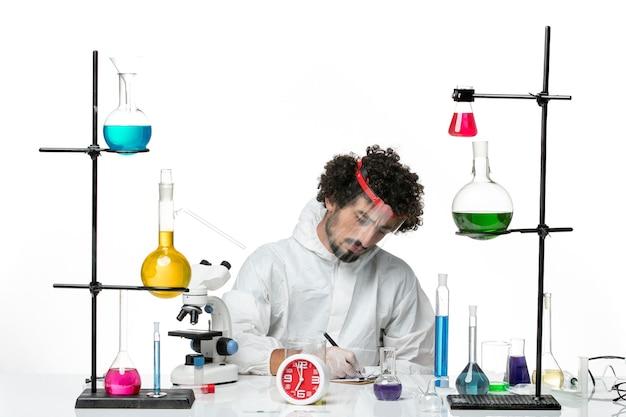 Вид спереди молодой ученый-мужчина в специальном костюме с защитным шлемом, пишущий заметки на белой стене