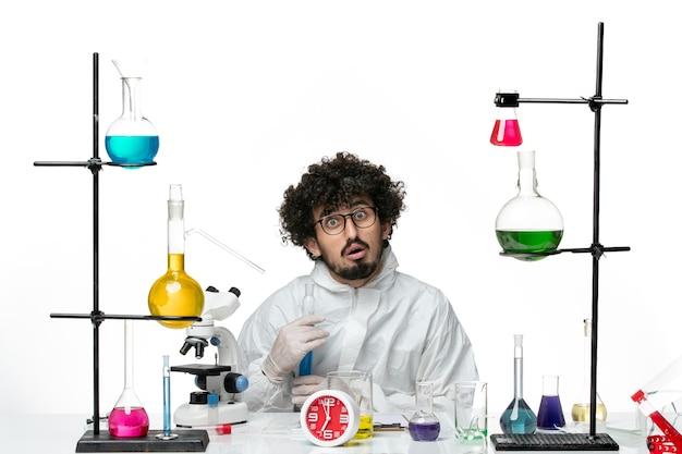 Вид спереди молодого ученого-мужчины в специальном костюме, держащего фляжку с раствором на белом столе