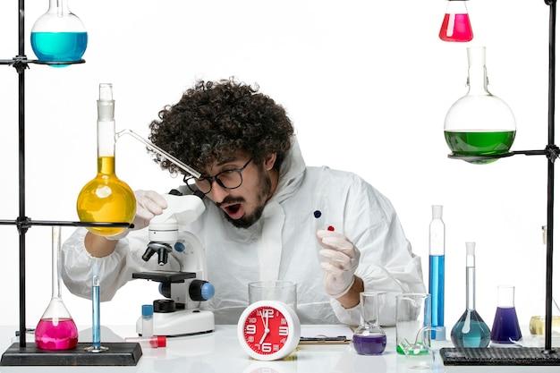サンプルを保持し、白い壁に顕微鏡を使用して特別なスーツを着た若い男性科学者の正面図