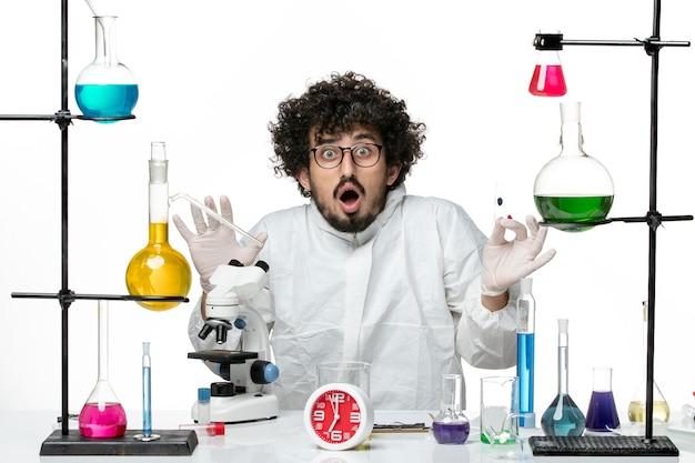 サンプルを保持し、明るい白い壁に顕微鏡を使用して特別なスーツを着た若い男性科学者の正面図