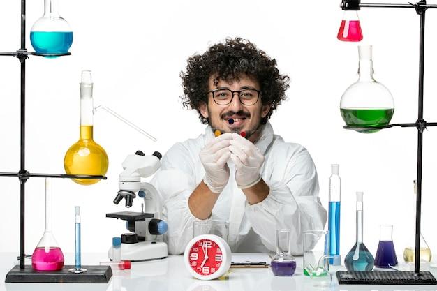 白い壁にサンプルを保持している特別なスーツの正面図若い男性科学者