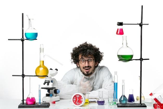真っ白な壁にソリューションと座っている特別なスーツを着た若い男性科学者の正面図