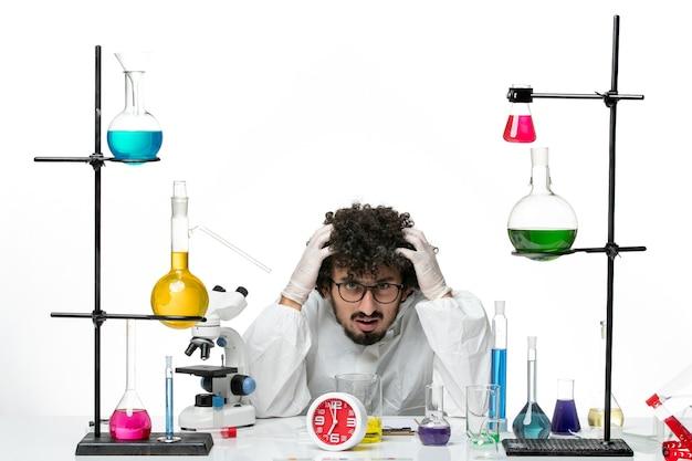 Вид спереди молодого ученого-мужчины в специальном костюме, сидящего с растворами на белой стене