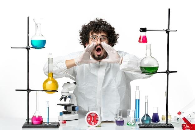 白い壁の科学実験室のcovidパンデミック化学を要求する解決策でテーブルの周りに立っている特別なスーツを着た若い男性科学者の正面図