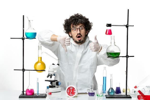明るい白い壁にソリューションとテーブルの周りに立っている特別なスーツを着た若い男性科学者の正面図