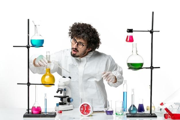 밝은 흰색 벽에 솔루션 테이블 주위에 서있는 특별한 정장에 전면보기 젊은 남성 과학자