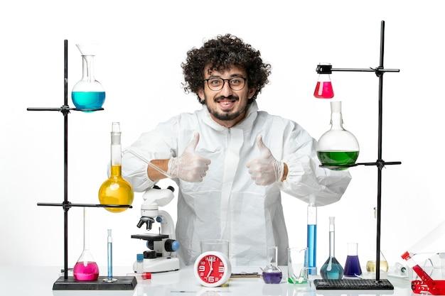白い壁に解決策とテーブルの周りに立っている特別なスーツを着た若い男性科学者の正面図