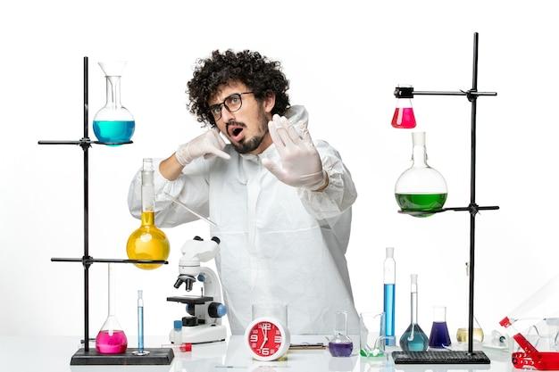 흰색 바닥에 솔루션 테이블 주위에 서있는 특별한 소송에서 전면보기 젊은 남성 과학자