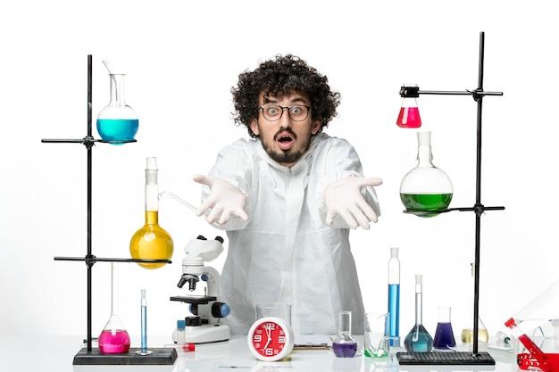 흰 벽에 솔루션 테이블 주위에 서있는 특별한 소송에서 전면보기 젊은 남성 과학자