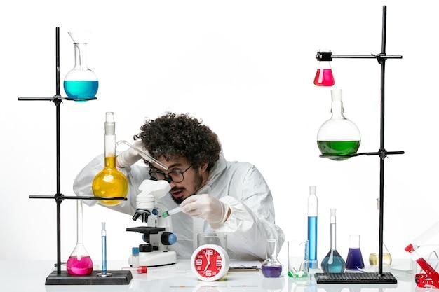 白い壁に顕微鏡を使用して特別なスーツを着た若い男性科学者の正面図