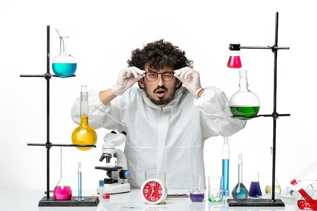 白い壁の実験室でサングラスをかけている特別なスーツを着た若い男性科学者の正面図