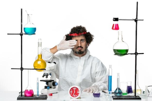 保護ヘルメットを着用し、白い机の科学実験室のcovid男性化学に取り組んでいる特別なスーツを着た若い男性科学者の正面図