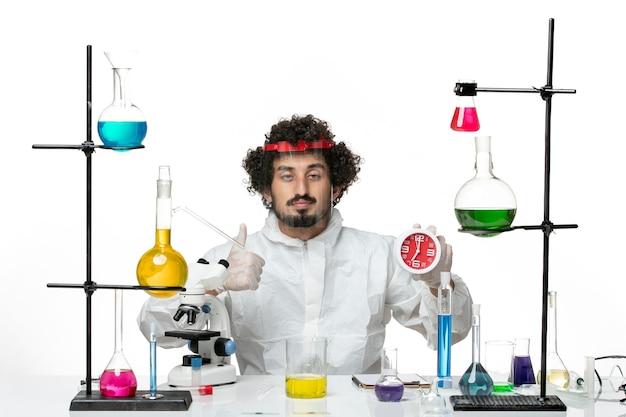 白い壁に時計を保持している保護ヘルメットと特別なスーツを着た若い男性科学者の正面図科学実験室covid化学男性