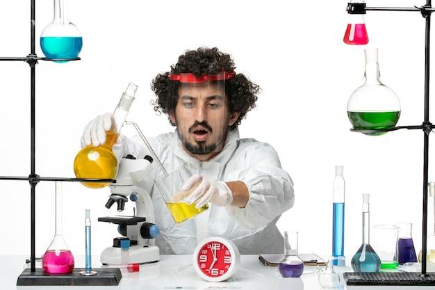 白い壁の科学実験室の共同化学の男性に保護ヘルメット混合ソリューションを備えた特別なスーツを着た若い男性科学者の正面図