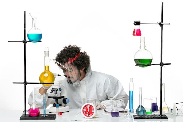 흰 벽 과학 실험실 covid 화학 남성에 현미경을 사용하여 보호 헬멧과 특수 소송에서 전면보기 젊은 남성 과학자