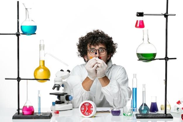 흰 벽에 솔루션 테이블 주위에서 작업하는 특별한 소송에서 전면보기 젊은 남성 과학자