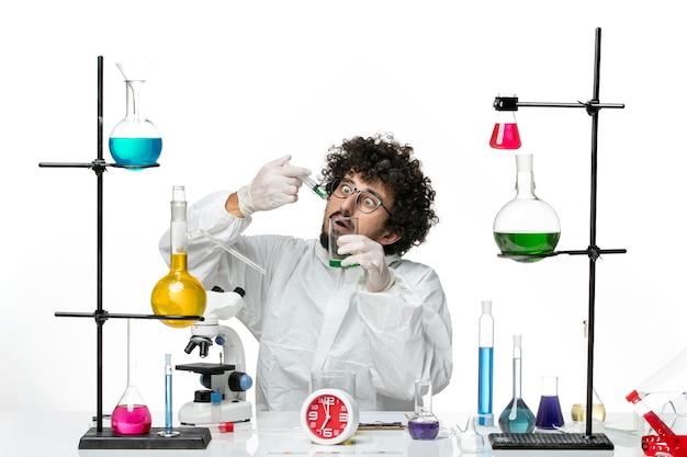 白い壁に注射と溶液を扱う特別なスーツを着た若い男性科学者の正面図