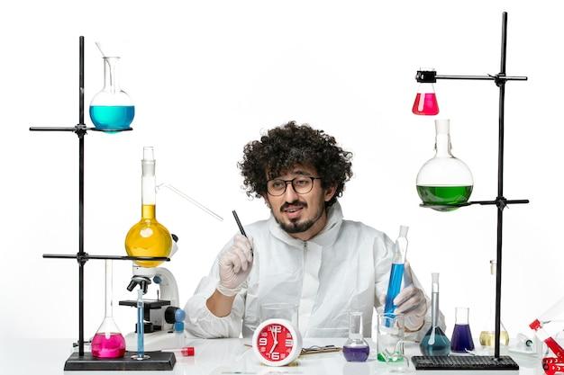 파란색 솔루션을 잡고 메모를 작성하는 흰색 특수 소송에서 전면보기 젊은 남성 과학자