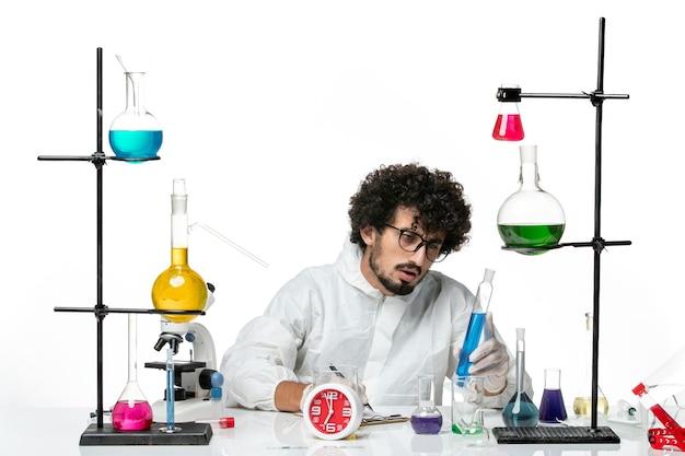 파란색 솔루션을 들고 흰색 특수 소송에서 전면보기 젊은 남성 과학자