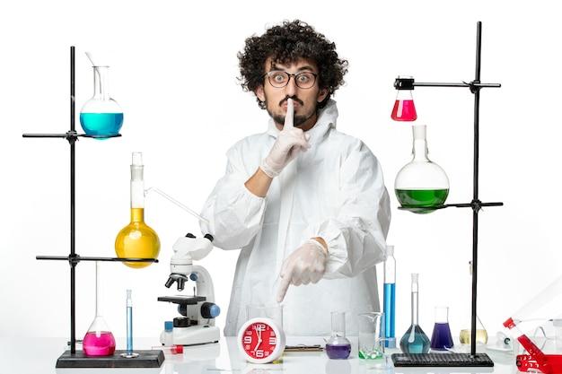 Вид спереди молодой ученый-мужчина в белом специальном костюме позирует