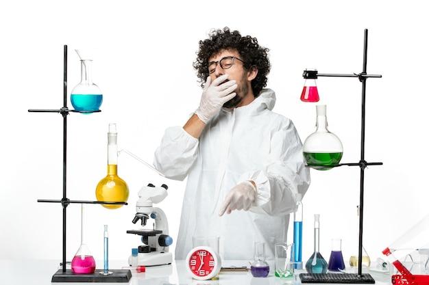 疲れを感じて解決策とテーブルの周りに立っている白い特別なスーツの正面図若い男性科学者