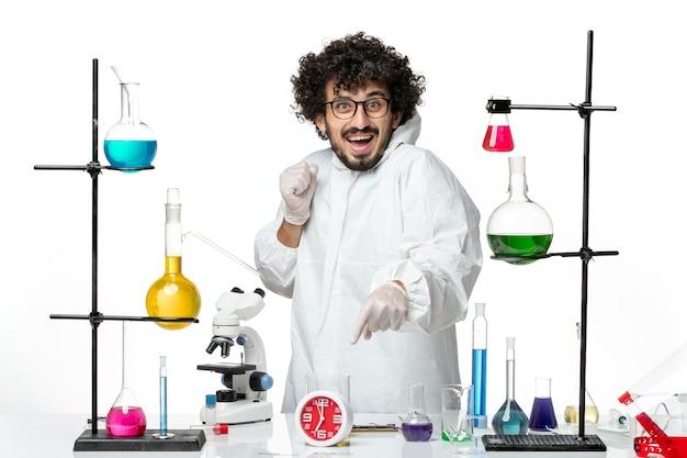 솔루션 웃음과 함께 테이블 주위에 서있는 흰색 특수 정장에 전면보기 젊은 남성 과학자