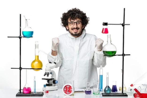 解決策を喜んでテーブルの周りに立っている白い特別なスーツを着た若い男性科学者の正面図