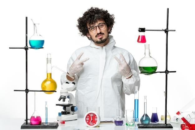 解決策とテーブルの周りに立っている白い特別なスーツの正面図若い男性科学者