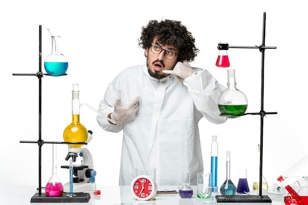 솔루션 테이블 주위에 서있는 흰색 특수 정장에 전면보기 젊은 남성 과학자