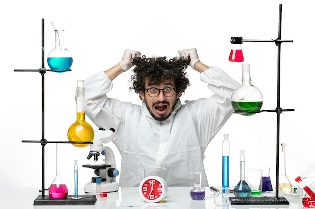 Вид спереди молодой ученый-мужчина в белом специальном костюме, рвущий волосы