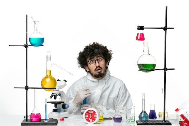 Front view young male scientist in special suit holding flask with solution on white desk