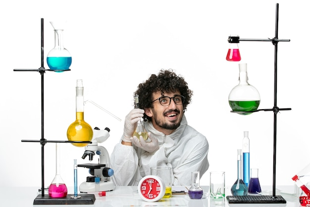Front view young male scientist in special suit holding flask with solution on the white wall