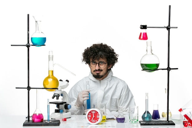 Front view young male scientist in special suit holding flask with solution on white wall