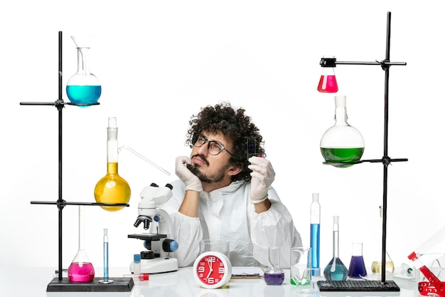 Front view young male scientist in special suit holding samples and thinking on white wall