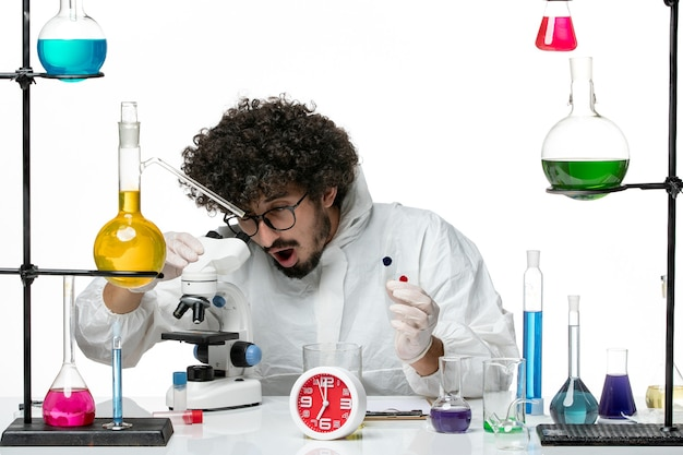 Front view young male scientist in special suit holding samples and using microscope on a white wall