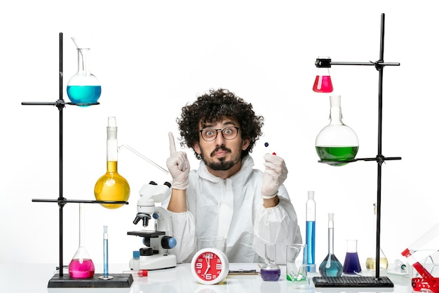 Front view young male scientist in special suit holding samples on a white wall
