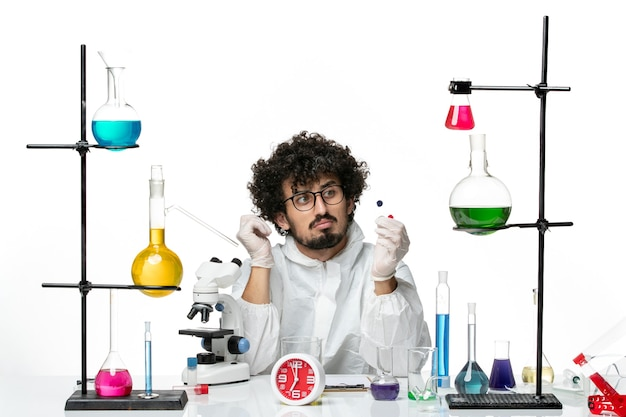 Front view young male scientist in special suit holding samples on white wall